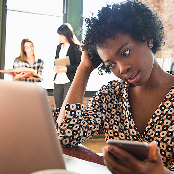 Woman holding phone and looking at laptop