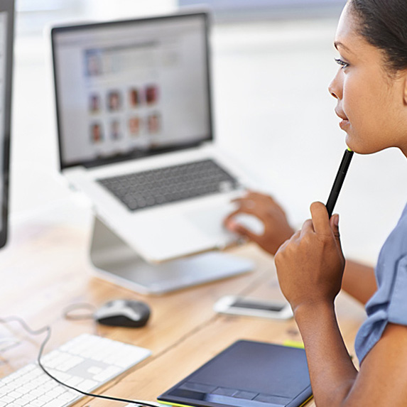 Woman working on computer and laptop