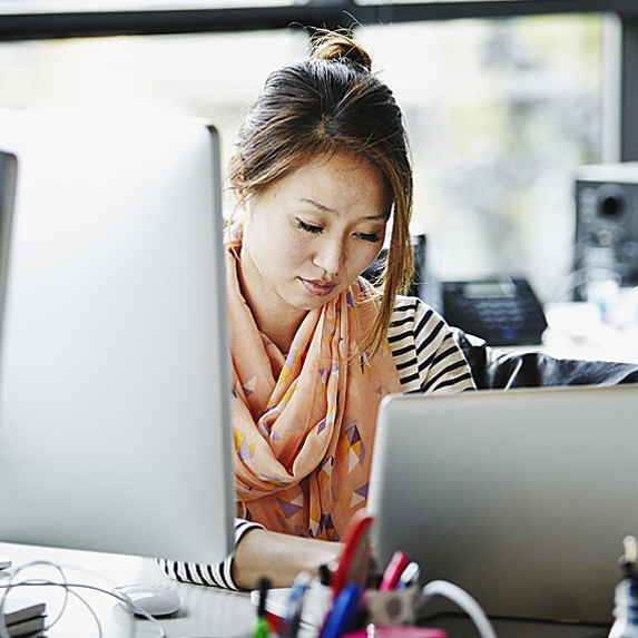 Woman working on computer and tablet