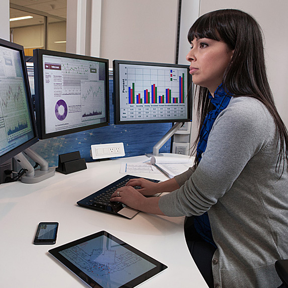 Woman typing on keyboard with three monitors, tablet, phone