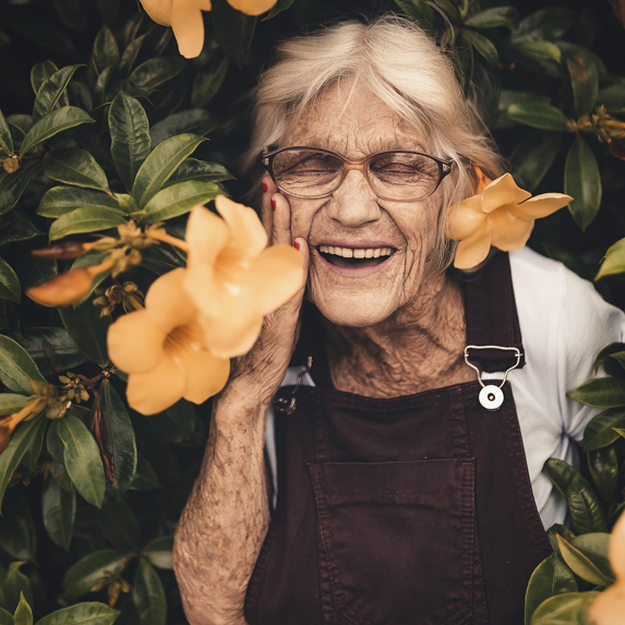 Older woman wearing overalls smiling widely