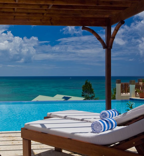 From two loungers under a shady covering, a view of the ocean
