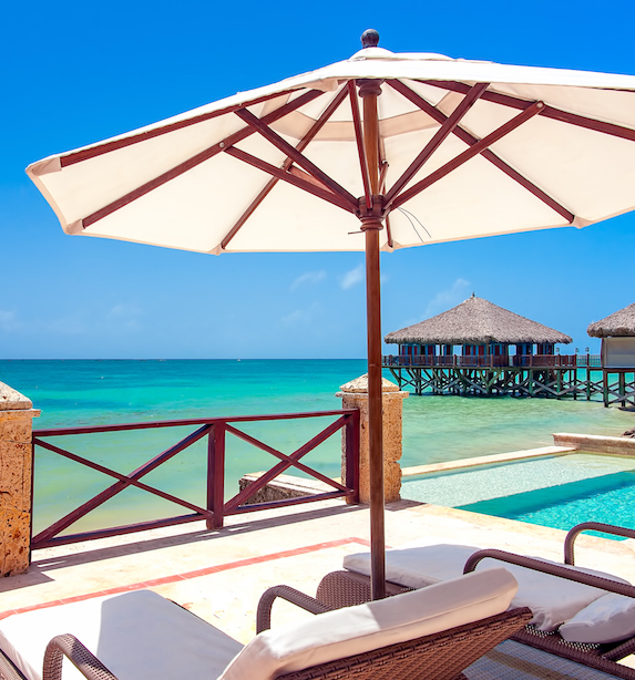 A white umbrella shades two white loungers overlooking tropical blue waters at a luxury resort