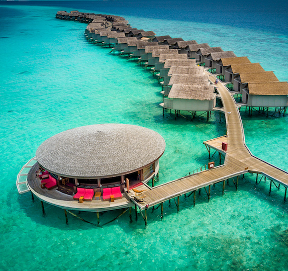 Luxury villas sit overtop the tropical waters of the Maldives