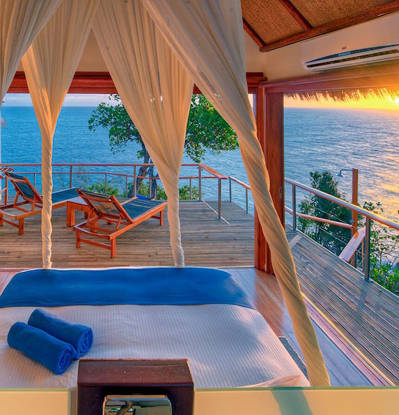 A luxurious resort bed faces a private deck overlooking tropical waters