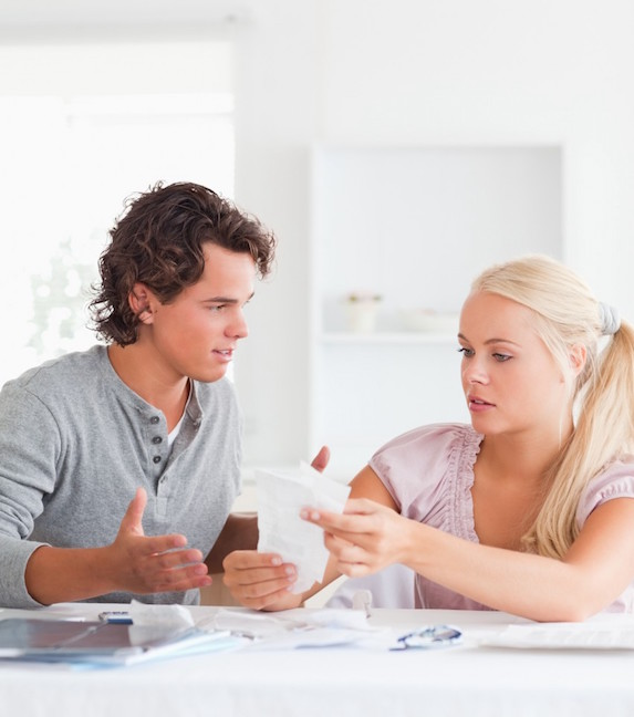 A young couple sits at a table in disagreement