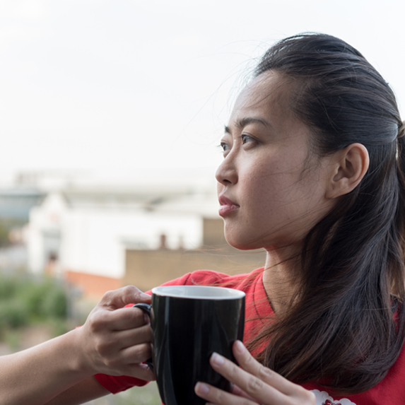 A woman holds a mug and a looks out into the distance thoughtfully