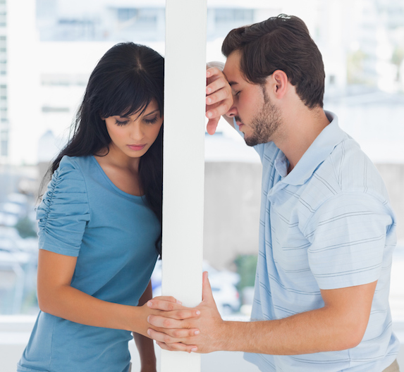 Man and woman stand on opposite sides of a wall, linking hands