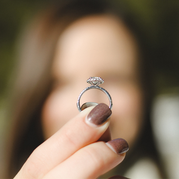 A woman holds a wedding ring in focus in front of her