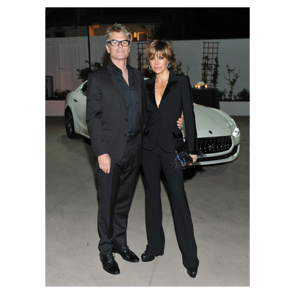 lisa and harry pose in front of a car