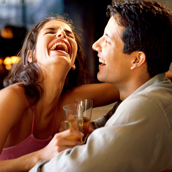 Woman and man laughing and drinking