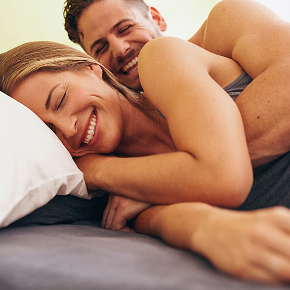 Man and woman laughing in bed