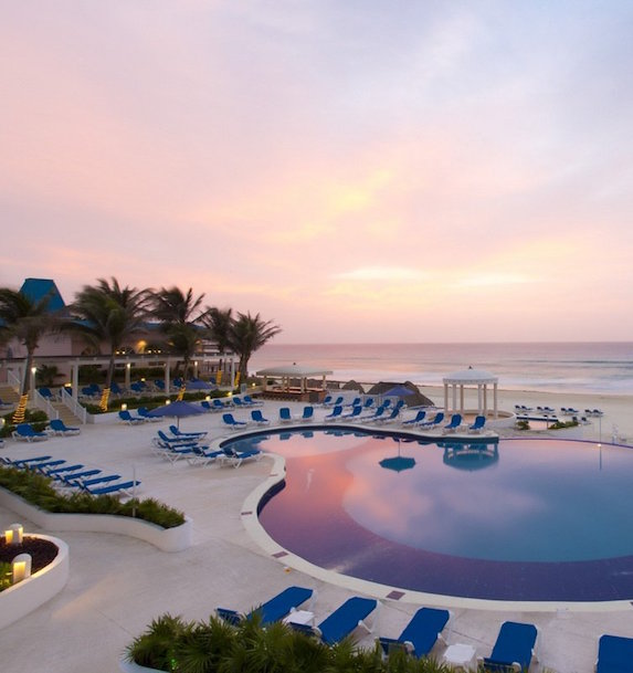 Sunset over a luxury resort pool surrounding by blue loungers