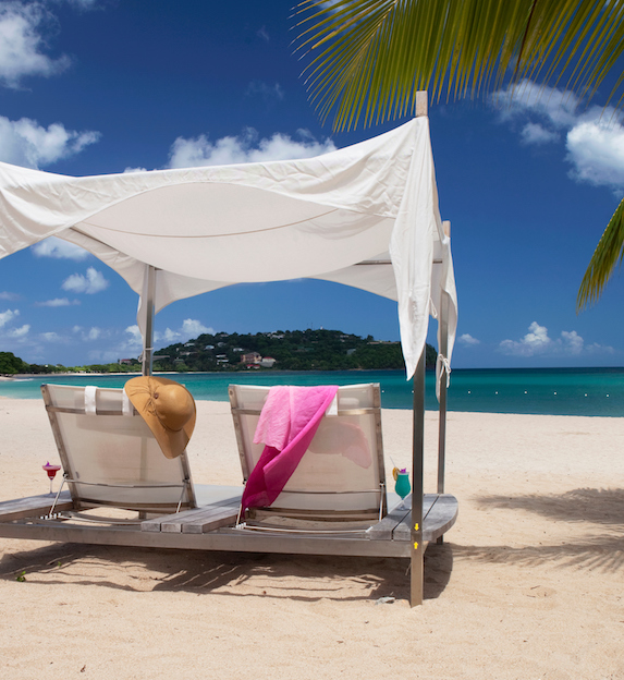 A pergola on a white sandy beach faces the tropical waters of St. Lucia