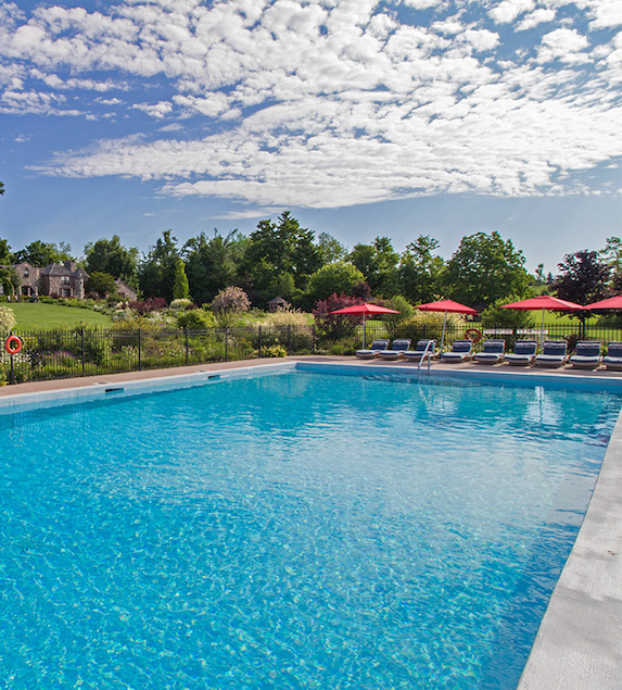 A view of the pool and loungers under a blue sky at Ste. Anne's spa