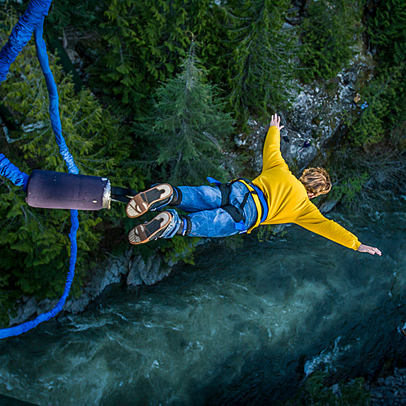 Person bungee jumping over river