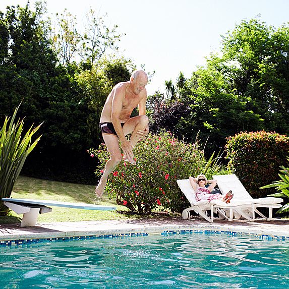 Older man jumping into pool while woman watches