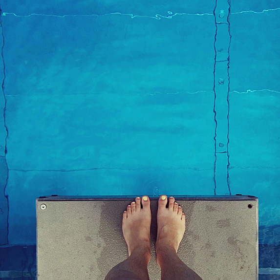 Overhead shot of feet on edge of platform above pool