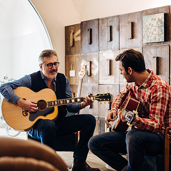 Young man teaching older man how to play guitar