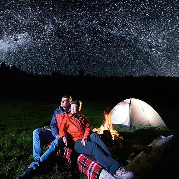 Couple next to tent looking up at stars