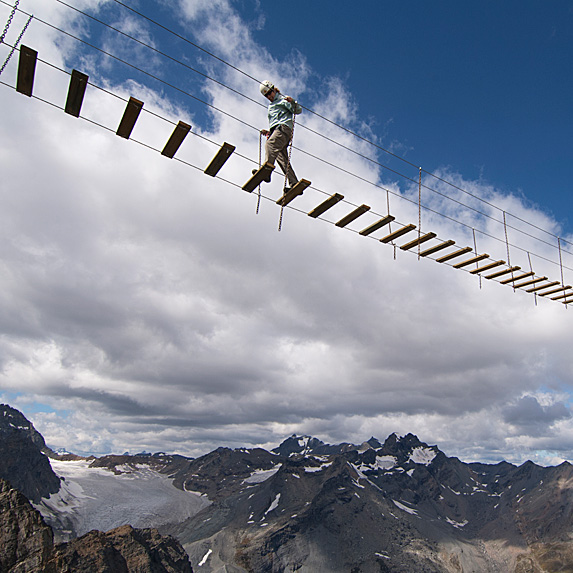 Person walking across suspension bridge