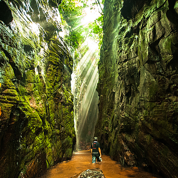 Man walking through a cave to a waterfall