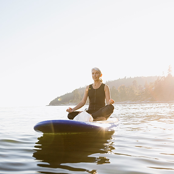 Older woman in resting pose on paddleboard