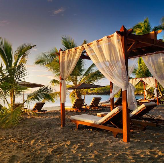 Sunset on the beach, where pergolas and palm tress line the beach
