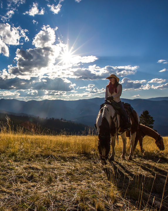 A woman sits horseback with another horse nearby on a picturesque mountain landscape
