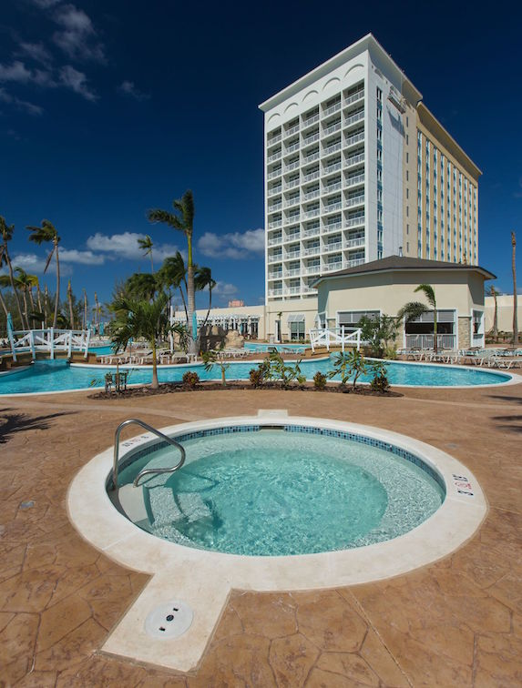 A jacuzzi hot tub with the resort pool and building in the background