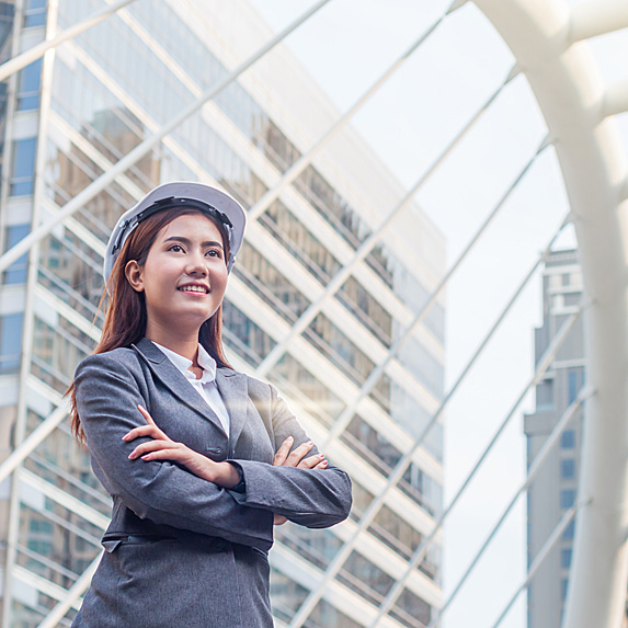 Woman wearing hardhat, smiling outside building