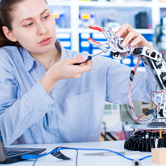 Woman working on robotic arm