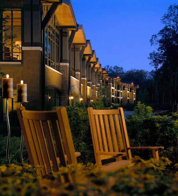 Cozy wood chairs sit in front of a well-lit Woodloch Lodge in the evening