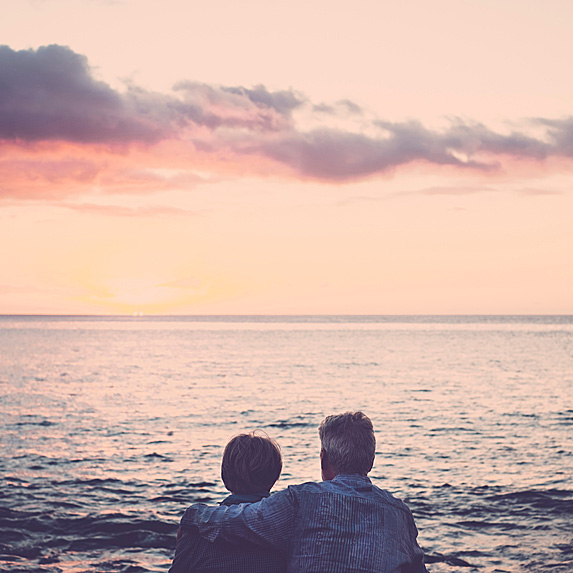 Older couple looking at sunset over ocean