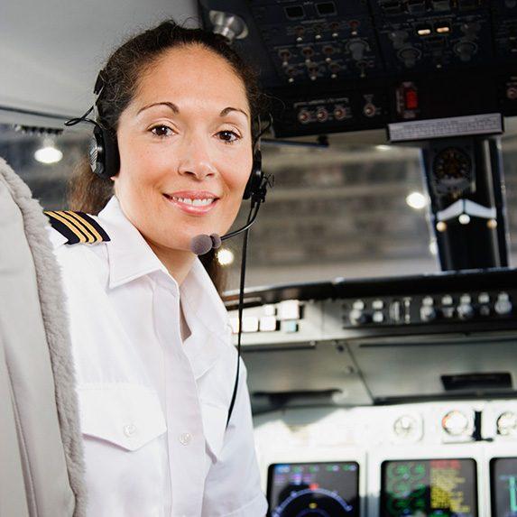 Female pilot smiles in plane