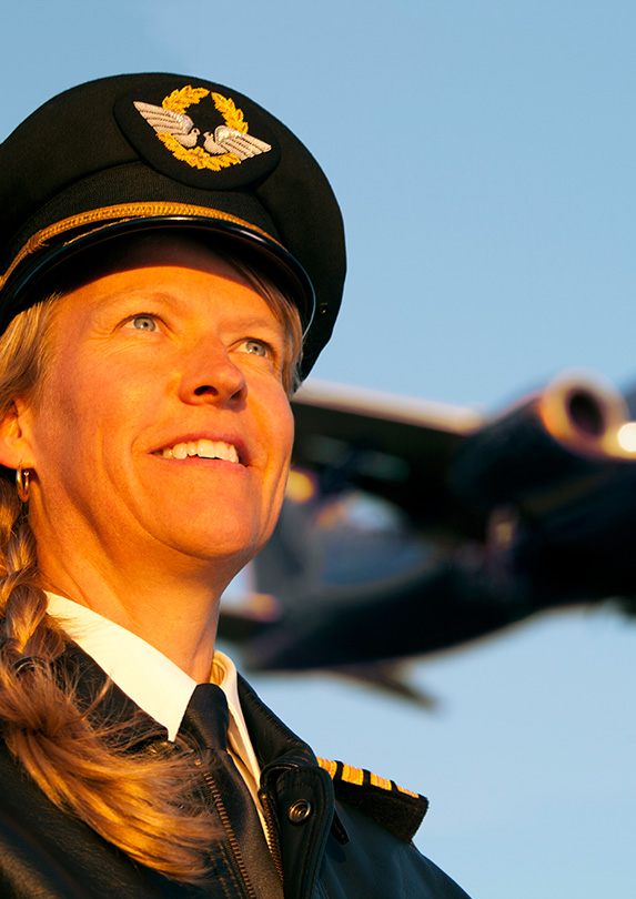Pilot smiles with plane in background