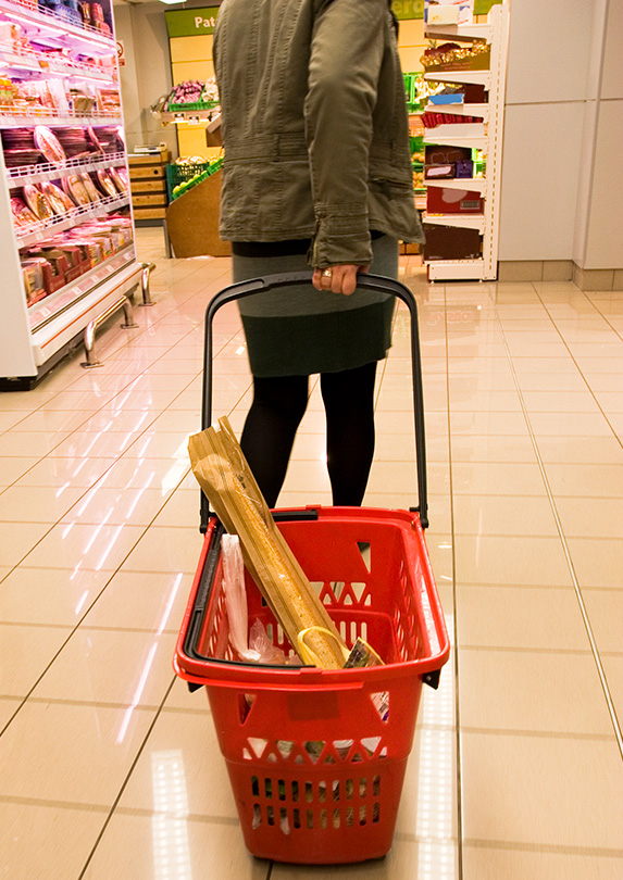 Customer pulling a shopping basket