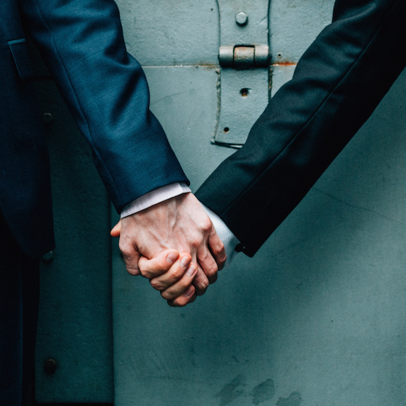 Mid-section of a gay couple holding hands