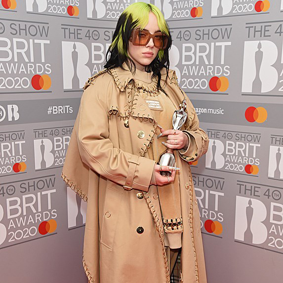 Billie Eilish on red carpet in trench coat