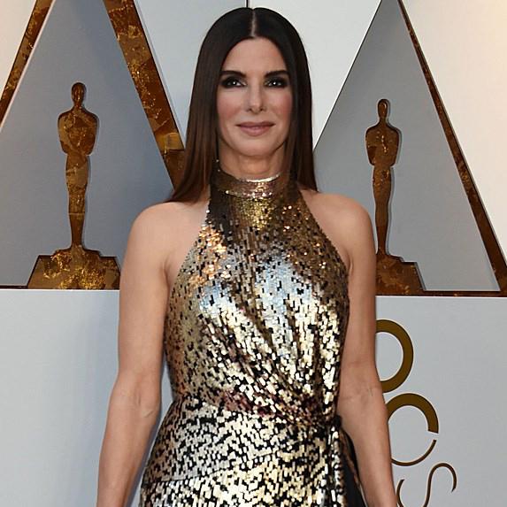 Sandra Bullock in gold dress on red carpet