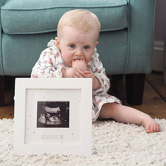 Baby with foot in mouth with pic of sonogram