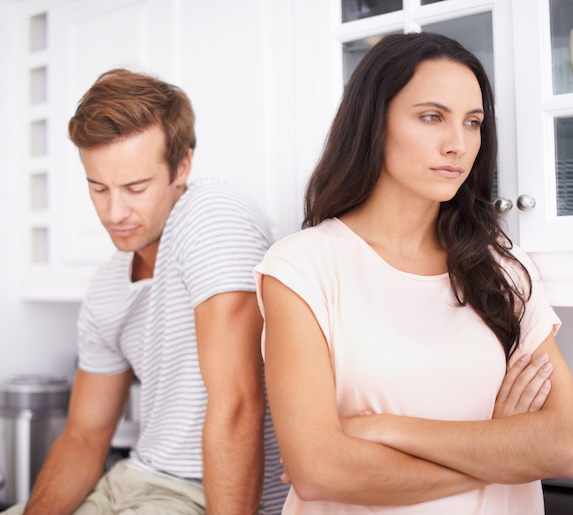 An unhappy couple stands in the kitchen, the woman turned away from the man with her arms crossed