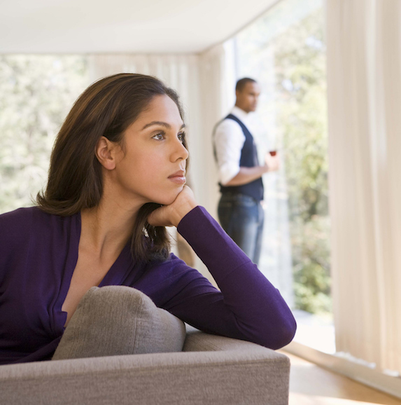 A woman sits in thought while a man in the background holding a glass of wine looks on
