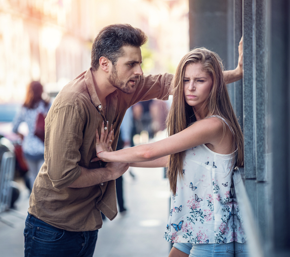 A young woman makes a frustrated face as she pushes away the man in front of her, who is leaning in angrily