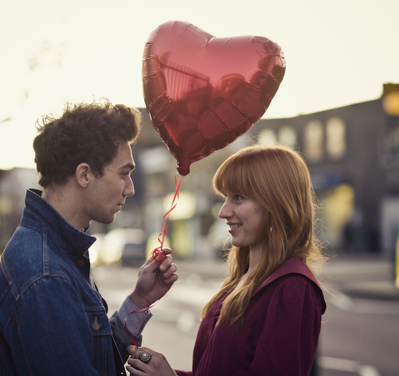 A man holds out a heart-shaped balloon as he stands closely to the woman in front of him