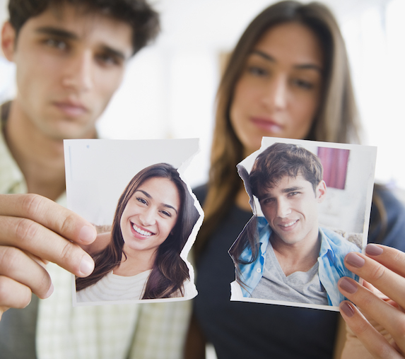 An unhappy couple stands next to one another, each holding a half of a torn photo of the two of them