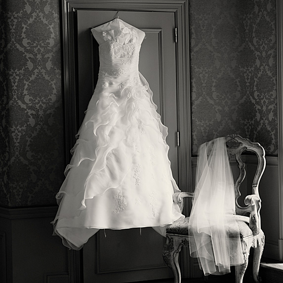 Wedding dress hanging on wall next to veil