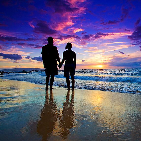 Couple on beach looking at stunning sunset