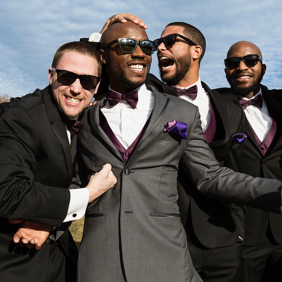 Groom laughing with three groomsmen