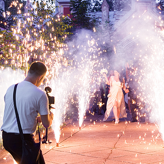 Videographer shooting bride and groom amidst pyrotechnics
